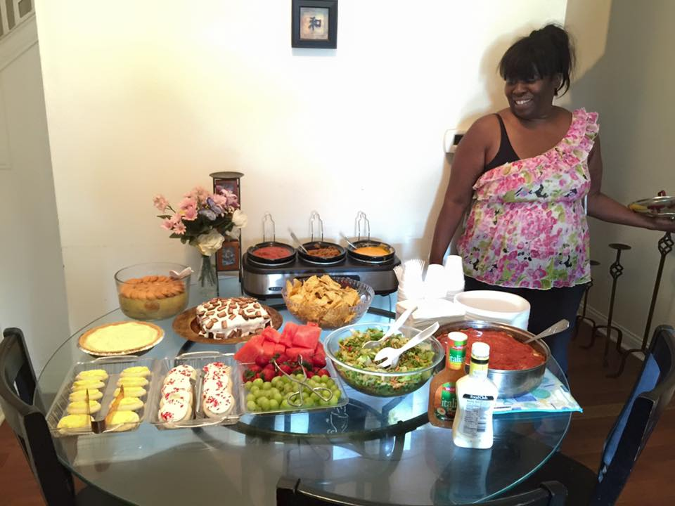 A photo of Ms. Sarah standing beside a table of food she has prepared for youth at Broadway United Methodist Church in Indianapolis, Indiana.