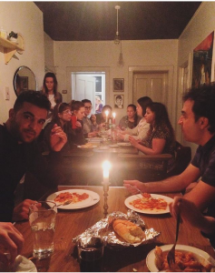 Photo of guests eating around the dinner table at Ryan Cook's home in Liverpool, England.