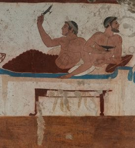 A fresco panting of two men reclining on a couch behind a small table, representing the ancient style of eating at a symposium.