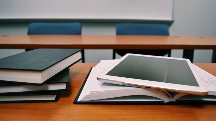 Image of desk with a stack of books on the left and an open book on the right with a rose gold iPad on top.