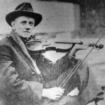 Black and white photograph of Fiddlin' John Carson featuring a seated white man wearing a black fedora and lighter colored jacket, holding a violin in playing position.