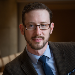 Headshot of Jesse P. Karlsberg with short brown hair, close-shaven beard, and glasses, wearing a dark brown suit jacket with light blue collared shirt and dark blue tie, against a dark brown backdrop.