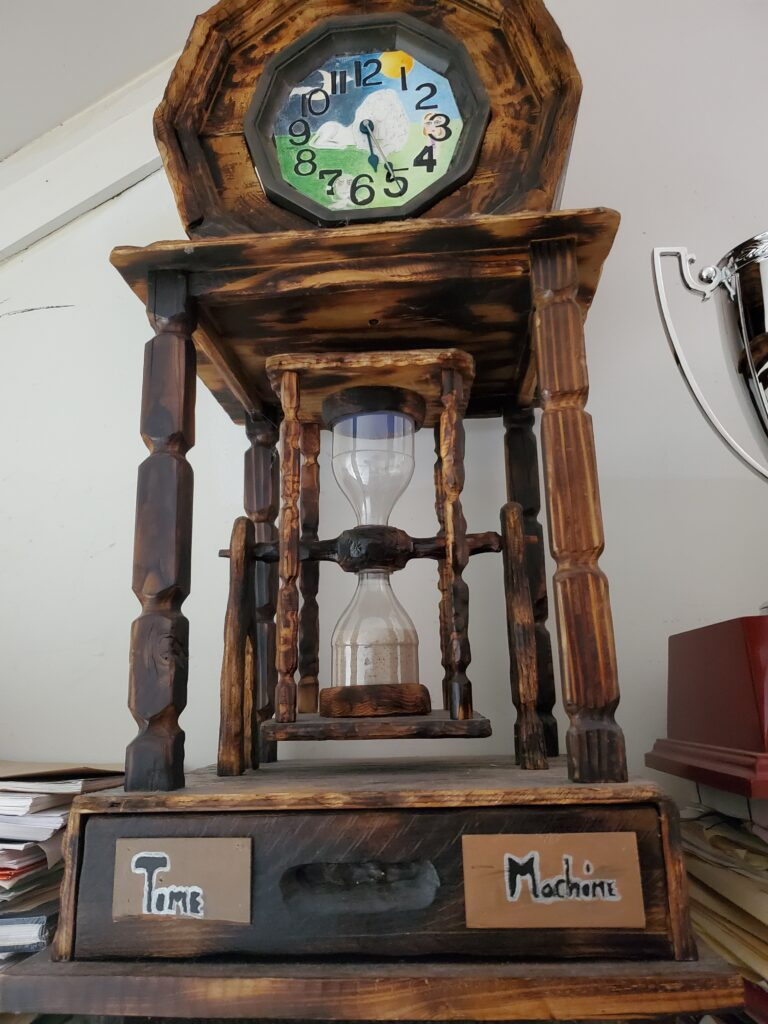 Handmade wooden hourglass featuring hand-painted clock and plaque with words Time Machine.