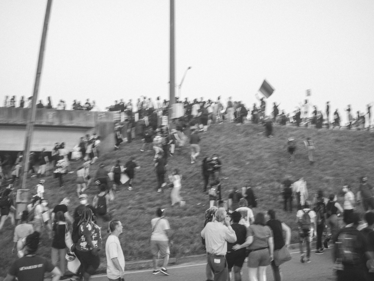 A black-and-white photo of around 70 people climbing up the grassy hill onto the interstate during the protests against the police killing of Rayshard Brooks