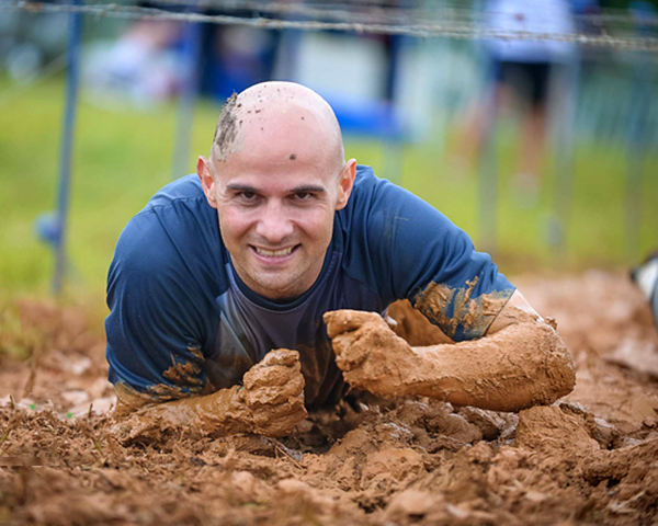 Photo of person doing an obstacle course in the mud
