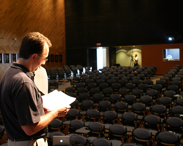 Photo of a man standing on the stage in an empty auditorium
