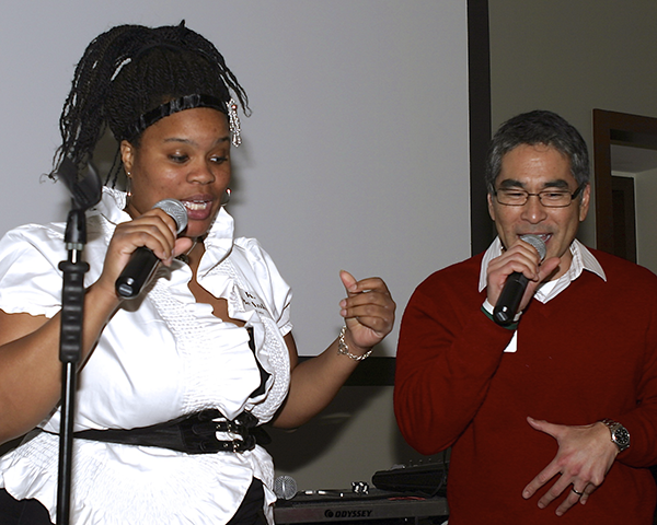 Photo of two people singing at a party