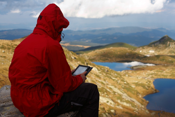 Photo of person sitting on a mountian with an iPad