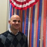 Photo of employee standing next to a decorated office