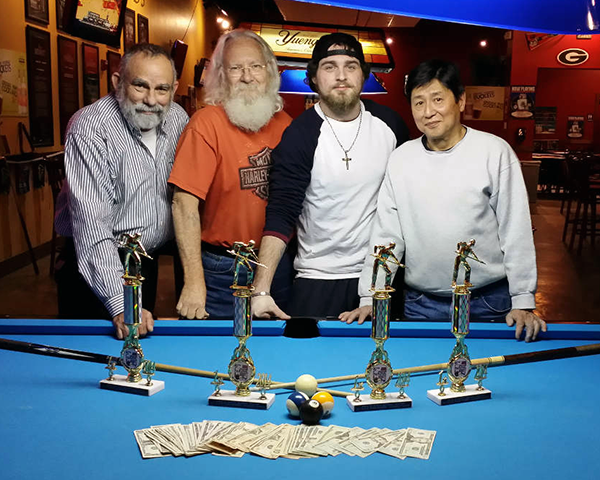 Photo of four men standing behind a pool table