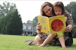 Photo of a mom reading a book to her daughter