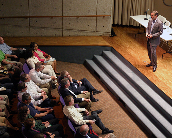 Photo of a speaker on an auditorium stage