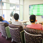 Photo of three students playing a video game