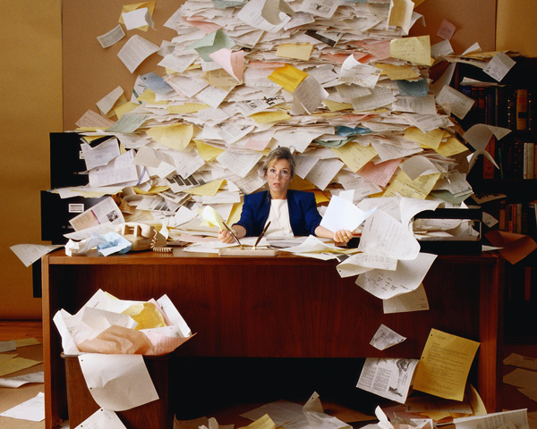 employee with a mountain of paper on her desk