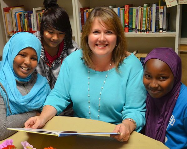 Photo of a volunteer reading to children