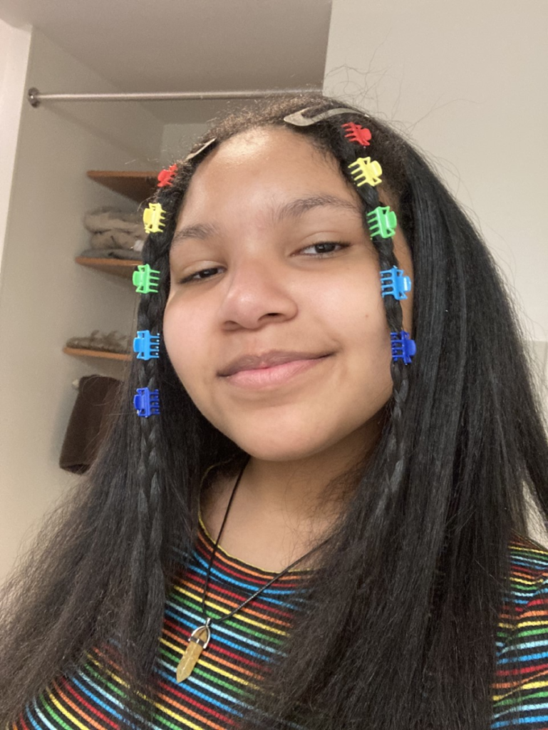 Young woman smiles at the camera. She has long black hair clipped back with rainbow clips on both sides of her head. She is wearing a rainbow striped shirt and a wood carving pendant.