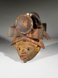 Mask/headdress composed of male face with beard and pierced eyes, topped by head-ware which includes sculpted drum resting on framework, held in place by sculpted fabric tie/CC Licensed