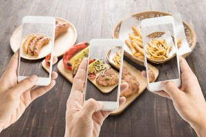 friends using smartphones to take photos of food.