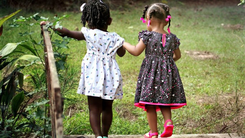 Image of two small girls walking together. The girls have their hair in braids and they are holding on to each other. One girl has her left hand on a wooden railing.