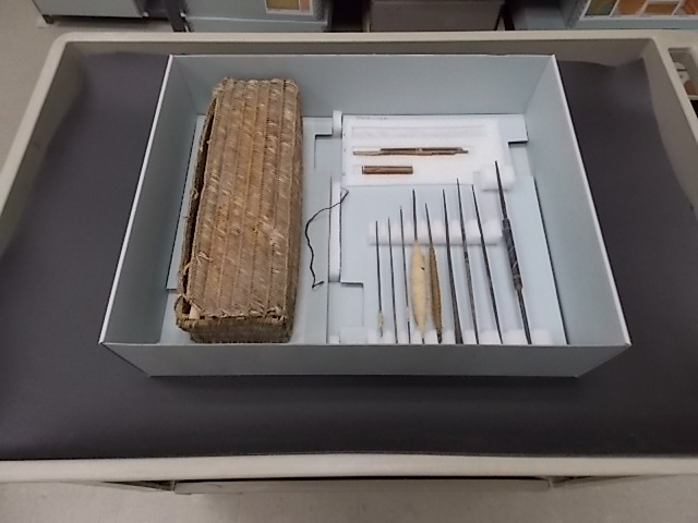 The spinning basket is on the left, made of woven reeds. The spinning supplies to the right include spindles, some wound with spun cotton and some empty. Everything is placed in a special box designed to hold this object and its many parts.