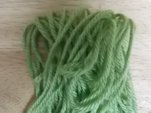 a pile of green commercial acrylic yarn resting on a wooden background