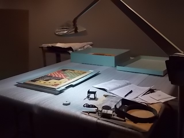 This is a picture of my research space in the museum. There is an overhead lamp to the right of the table so I can see the textile. I keep my tools in a pile next to the lamp with the textile a safe distance away.