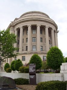 A photo of the Federal Trade Commission Building in Washington, DC, during daylight hours. A sign identifying the building is in the foreground along with green shrubbery.