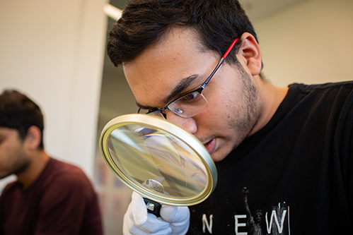 Sumedh Khanolkar handles and examines a photo using cotton gloves and a magnifying glass in the Rose Library.