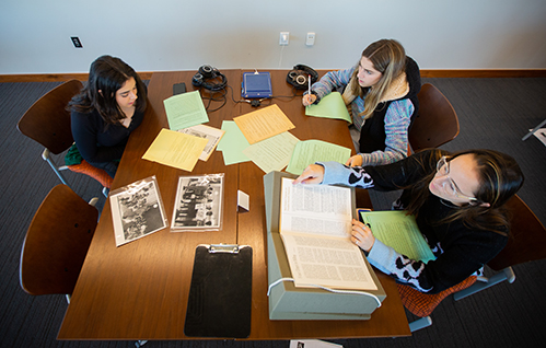 From left, Noufissa Guennoun, Jessica Grauberd, and Rachel Zipin pore over Rose Library archive materials on civil rights protests at Emory and desegregation opposition in Atlanta.