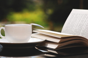 a coffee cup and an open book