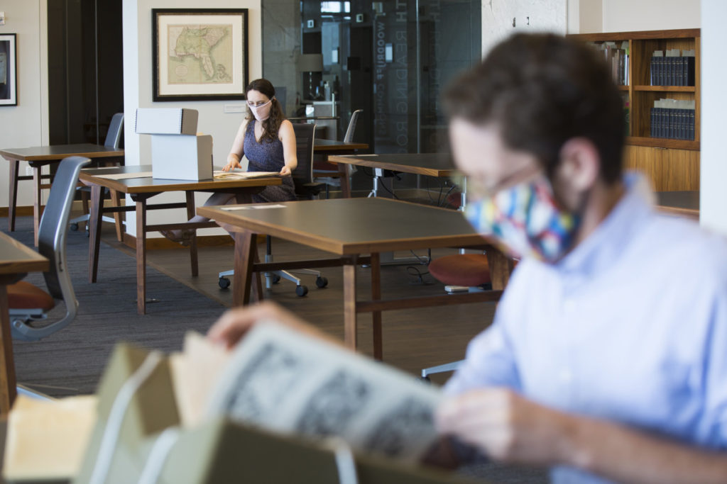 Researchers in the Rose Library wear masks as they peruse archival materials from socially distanced tables.