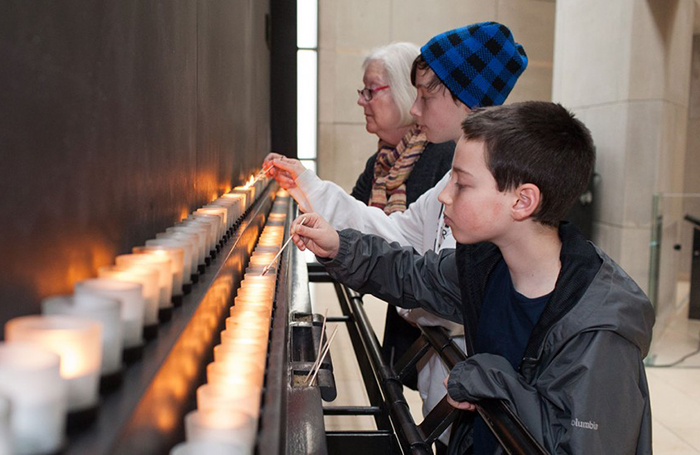 People light candles at the United States Holocaust Memorial Museum in Washington D.C. during the Days of Remembrance in 2014.