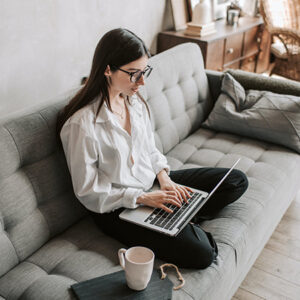 Girl in white blouse sitting on gray couch working on laptop computer. Image credit: Vlada Karpovich/Pexels